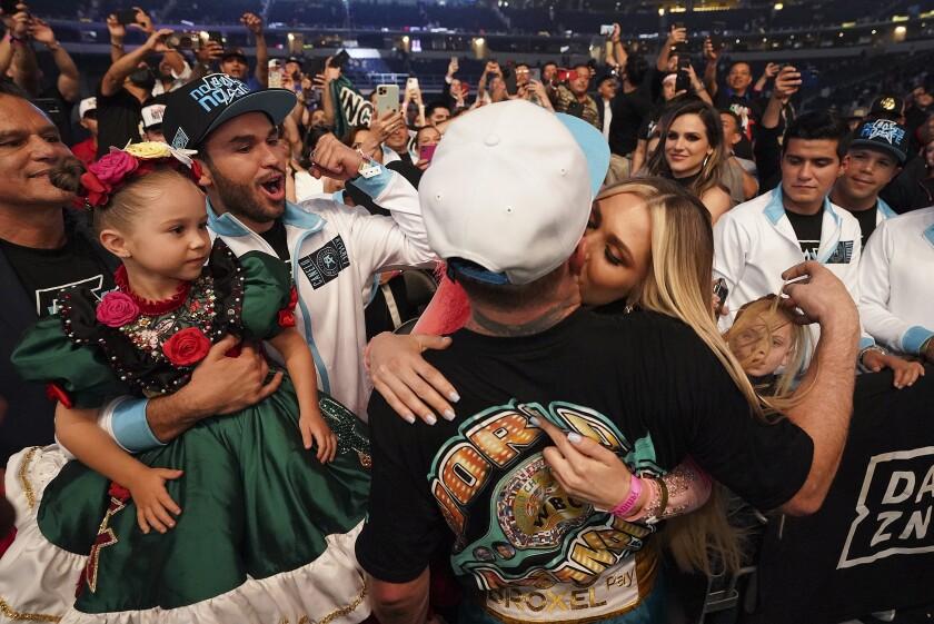 Canelo Alvarez kisses his girlfriend, Fernanda Gomez as their daughter, Maria