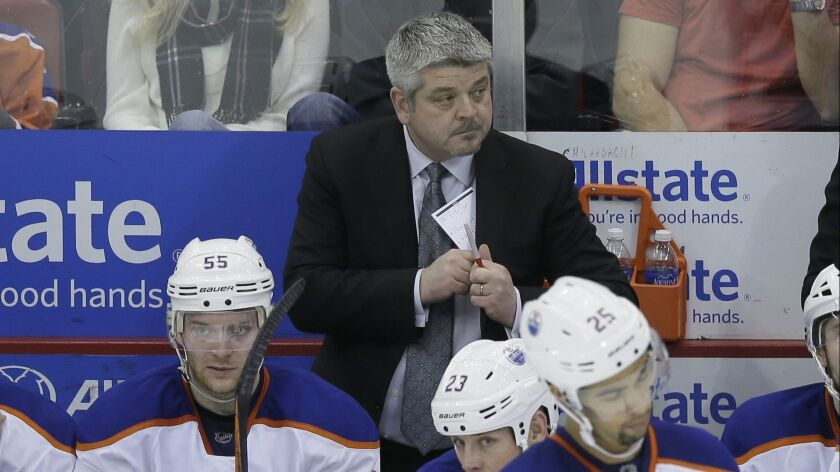 Todd McLellan watches from behind the Edmonton Oilers' bench during a game against the Detroit Red Wings in 2015.