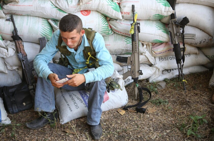 A member of a self-defense group sits next to sandbags in Antunez, in Michoacan state, Mexico.
