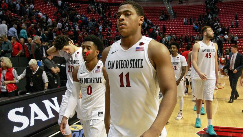 Jordan Schakel, Devin Watson, Matt Mitchell (left to right) walk off the court after blowing a late lead last Wednesday in a 77-73 loss against Fresno State at Viejas Arena.