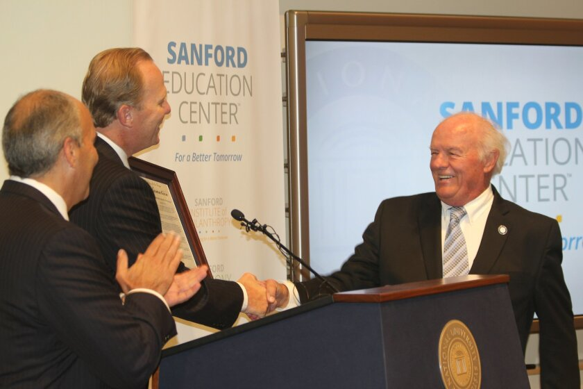 San Diego Mayor Kevin Faulconer (center) welcomes T. Denny Sanford to the podium during a grand opening celebration for Sanford Education Center in La Jolla.