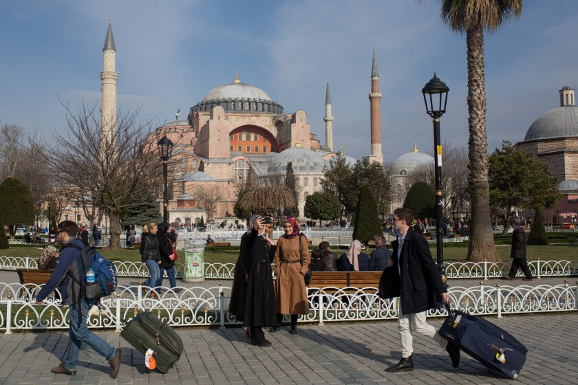 Tourists walk past the Hagia Sophia in Istanbul in a photo taken before the COVID-19 pandemic.