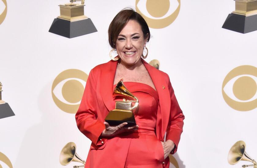 La argentina Claudia Brant posa en la sala de prensa del Grammy con el trofeo recibido.