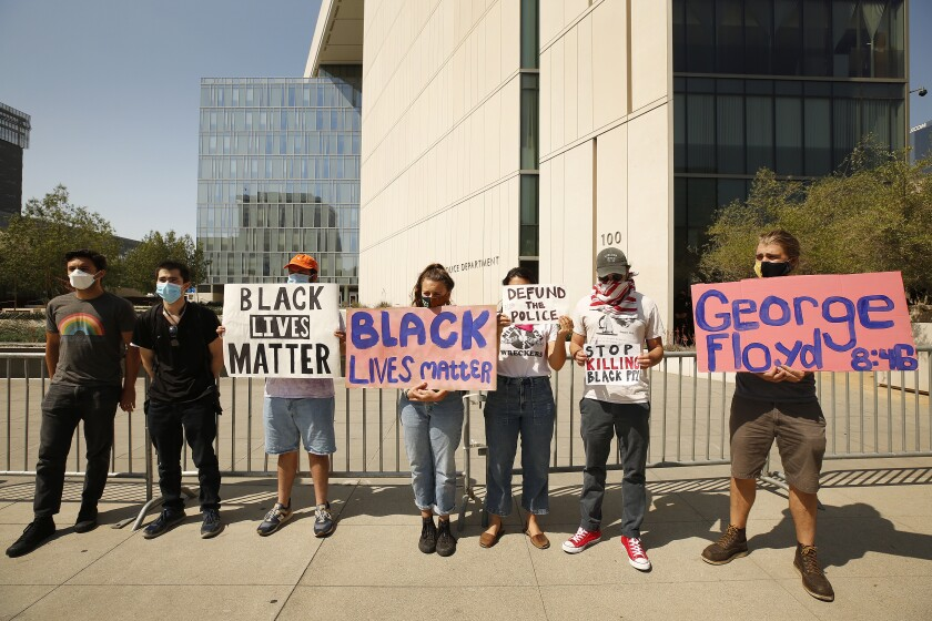 Protesters join a news conference by community activist Najee Ali in front of LAPD Headquarters on June 4.