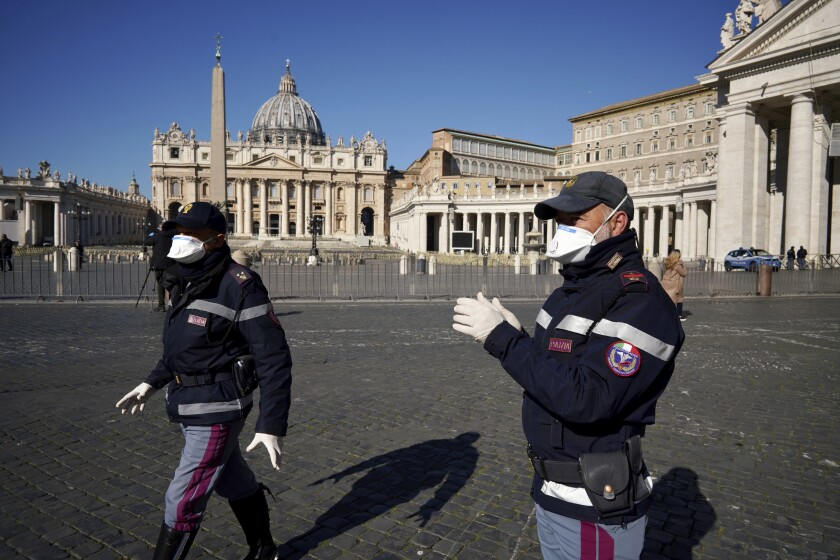 Police officers wearing masks patrol an empty St. Peter's Square at the Vatican, Wednesday, March 11, 2020.