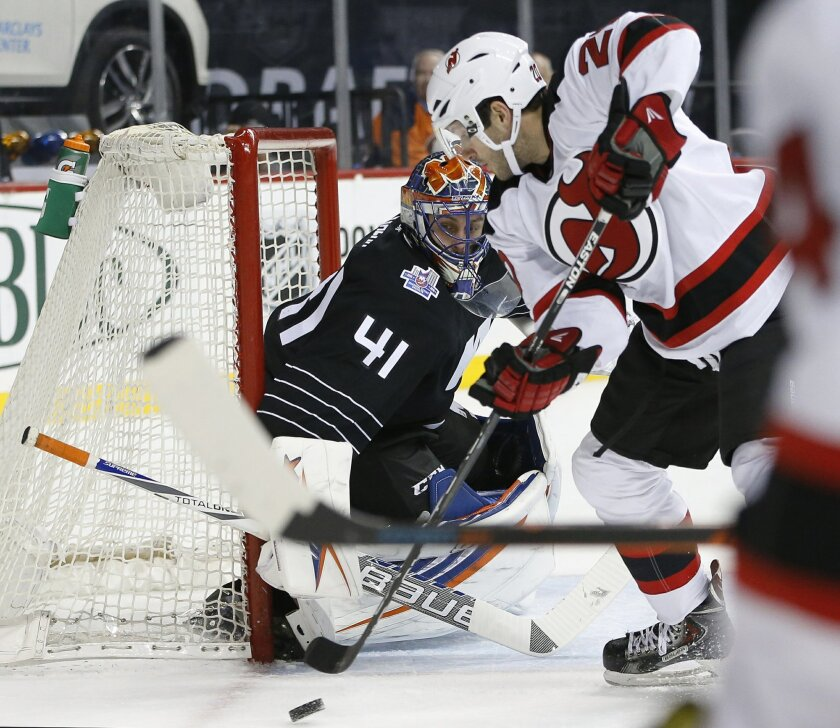 New York Islanders goalie Jaroslav Halak (41), of Slovakia, keeps his eyes on the puck New Jersey Devils right wing Lee Stempniak (20) threatens to score during the first period of an NHL hockey game in New York on Tuesday, Nov. 3, 2015. (AP Photo/Kathy Willens)