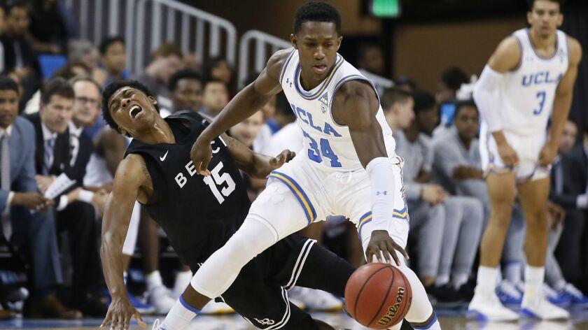UCLA guard David Singleton, right, keeps the ball away from Long Beach State guard Deishuan Booker d