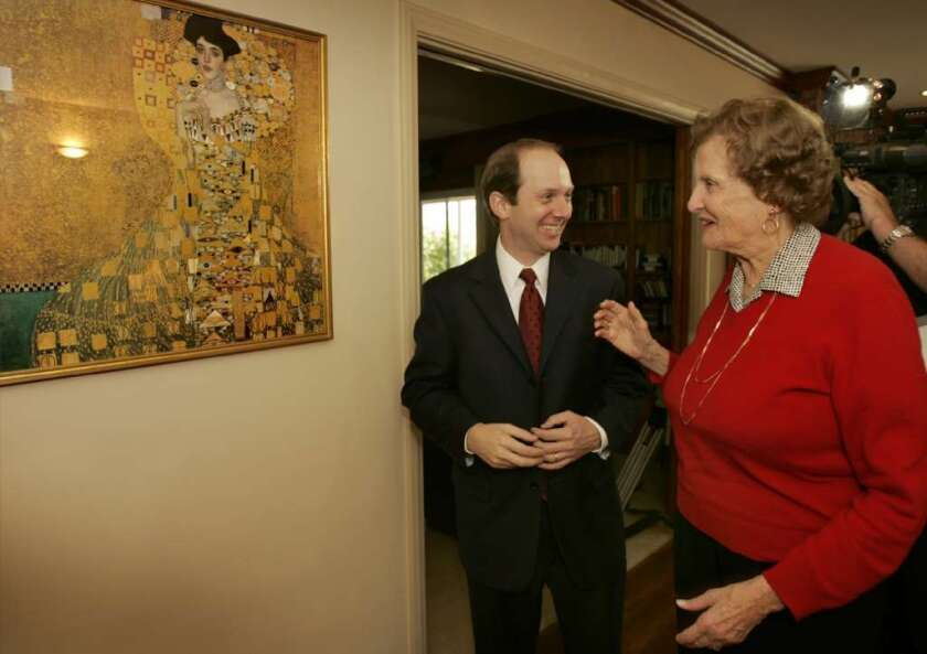 """Randol Schoenberg and Maria Altmann in 2006, standing beside a reproduction of Gustav Klimt's painting """"Portrait of Adele Bloch-Bauer I"""" that hung in her Los Angeles home."""