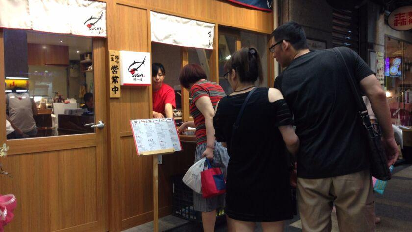 Taiwanese pedestrians examine the menu at a sushi restaurant in Taipei, Oct. 9, 2017.