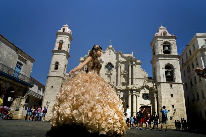 Foto de una quinceañera posando para el fotógrafo frente a una catedral donde turistas hacen fila para entrar, en La Habana. (AP Foto/Ramon Espinosa, File)
