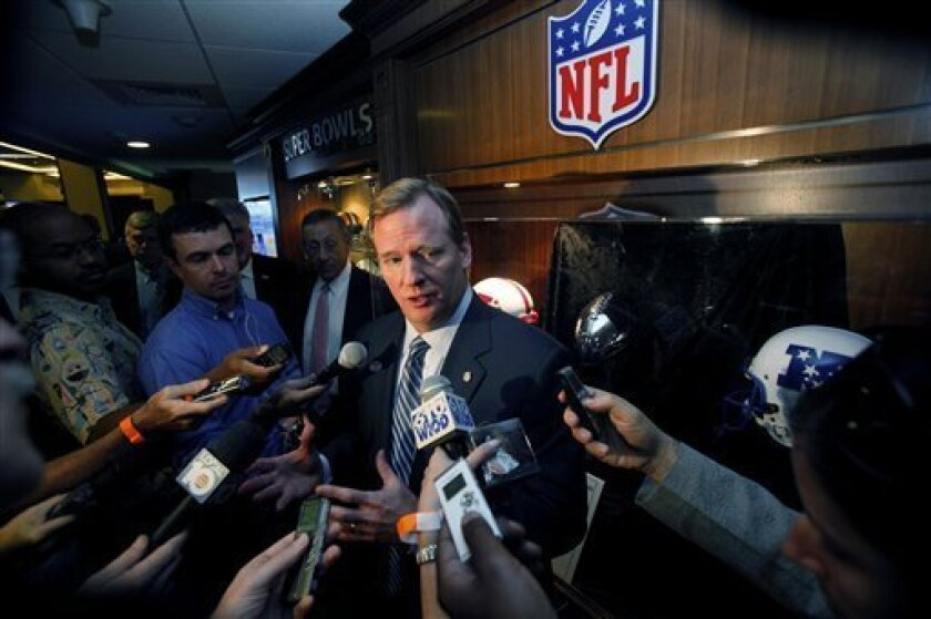 NFL football commissioner Roger Goodell, center, talks to reporters after attending a luncheon, Monday, Dec. 7, 2009 at Land Shark Stadium in Miami. (AP Photo/Wilfredo Lee)
