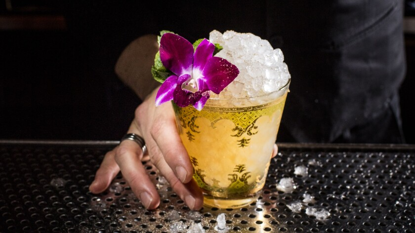 A cocktail from Death & Co. topped with crushed ice and a hibiscus flower.