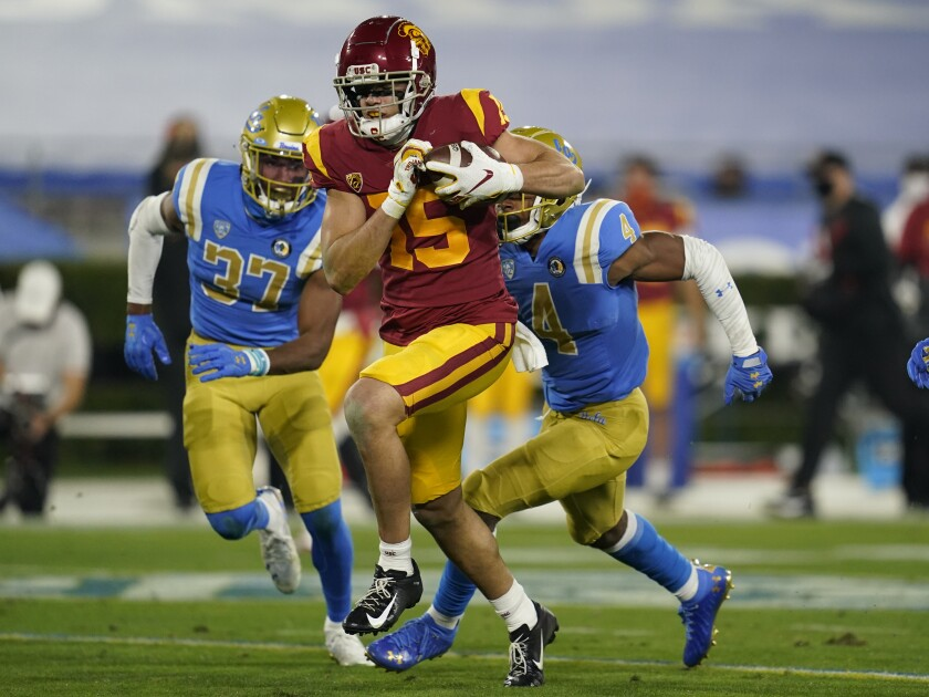 USC wide receiver Drake London runs to the end zone ahead of UCLA defenders.