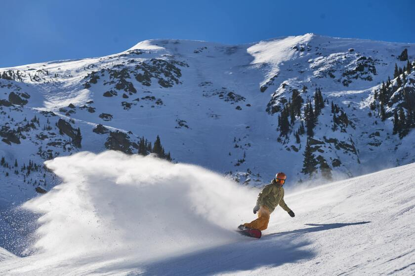 A snowboarder at Taos Ski Valley navigates the slopes in the resort's Kachina Basin, with the 12,481-foot-high Kachina Peak in the background.