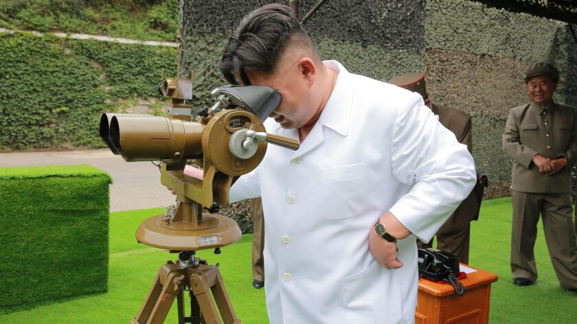 A photo distributed on Tuesday by North Korea purports to show leader Kim Jong Un looking through binoculars at the site of a ballistic missile launch at an undisclosed location in North Korea.