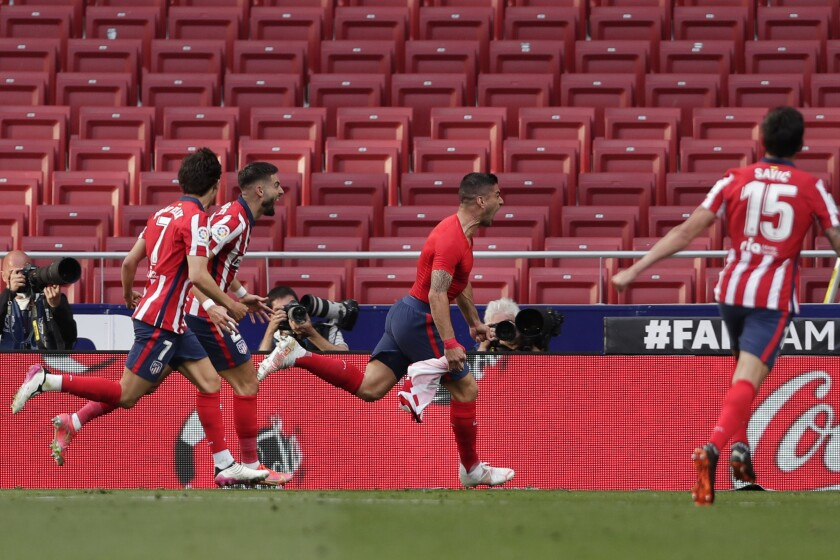 Atletico Madrid's Luis Suarez, right, celebrates after scoring his side's second goal during the Spanish La Liga soccer match between Atletico Madrid and Osasuna at the Wanda Metropolitano stadium in Madrid, Spain, Sunday, May 16, 2021. (AP Photo/Manu Fernandez)