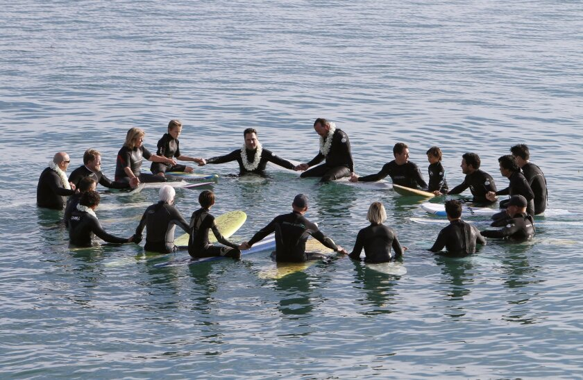 Mike McStay, center back, who is the brother of Joseph McStay, sits on his board sideways as he and friends and family members do a memorial paddle out for Joseph McStay, his wife Summer, and their children Gianni, 4, and Joey Jr., 3, whose remains were found in the desert near Victorville last No