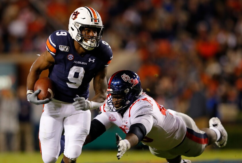 Auburn's Kam Martin (9) rushes past Mississippi's Josiah Coatney (40) in the first half on Saturday.
