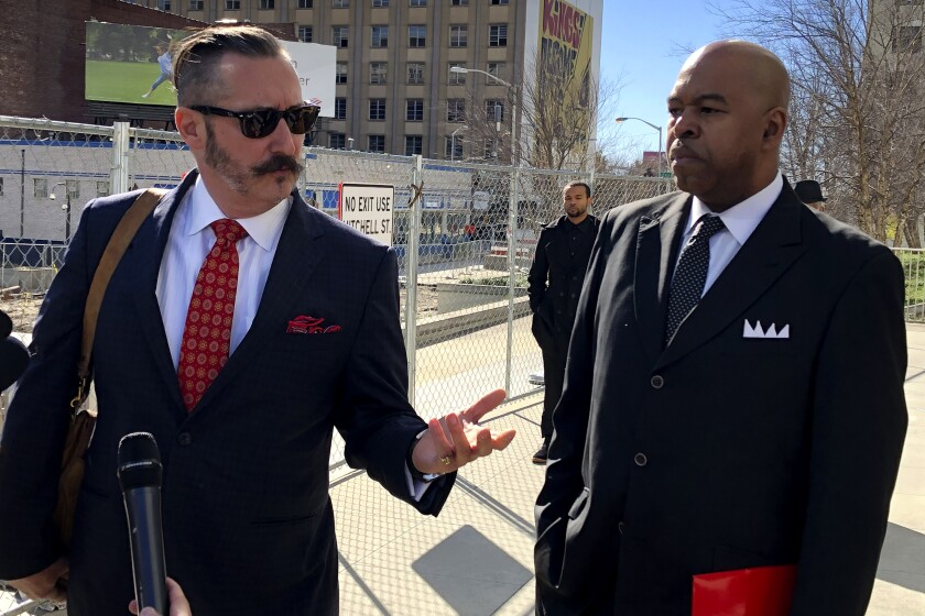 Attorney Stephen Murrin, right, speaks to reporters in front of the federal courthouse in Atlanta on Jan. 7, 2020, as his client, Larry Scott, looks on. Scott served as director of the city's Office of Contract Compliance and resigned before pleading guilty last year to charges of wire fraud and filing false tax returns. When he pleaded guilty in September, he admitted he failed to disclose outside consulting work and didn't report some income to tax authorities. He was sentenced Tuesday to serve two years in prison and to pay about $124,000 in restitution. (AP Photo/Kate Brumback)