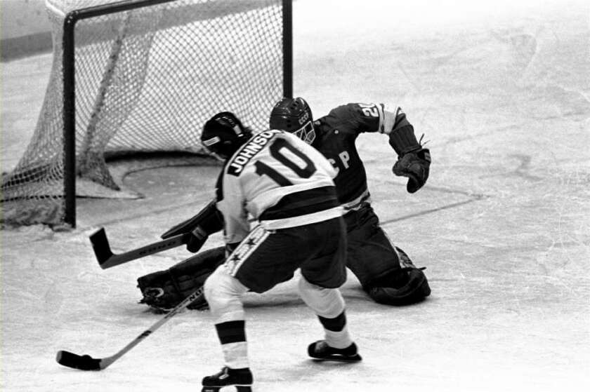 Hockey player Mark Johnson, left, prepares to shoot in the 1980 Miracle on Ice game, in which the underdog U.S. team defeated the Soviet Union team.