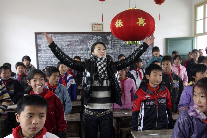 """Singer Tan Weiwei, center, gives a singing lesson to students in a rural primary school in Dabo village in Lianyuan city in southern China's Hunan Province on Dec. 4, 2007. Tan's latest song """"Xiao Juan,"""" has captivated many on the Chinese internet and has set off a discussion on domestic violence. (Chinatopix via AP)"""