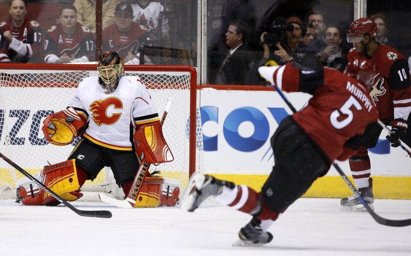 Calgary Flames' Jonas Hiller, left, of Switzerland, makes a glove-save on a shot by Arizona Coyotes' Connor Murphy (5) as Coyotes' Anthony Duclair (10) watches during the first period of an NHL hockey game Friday, Feb. 12, 2016, in Glendale, Ariz. (AP Photo/Ross D. Franklin)