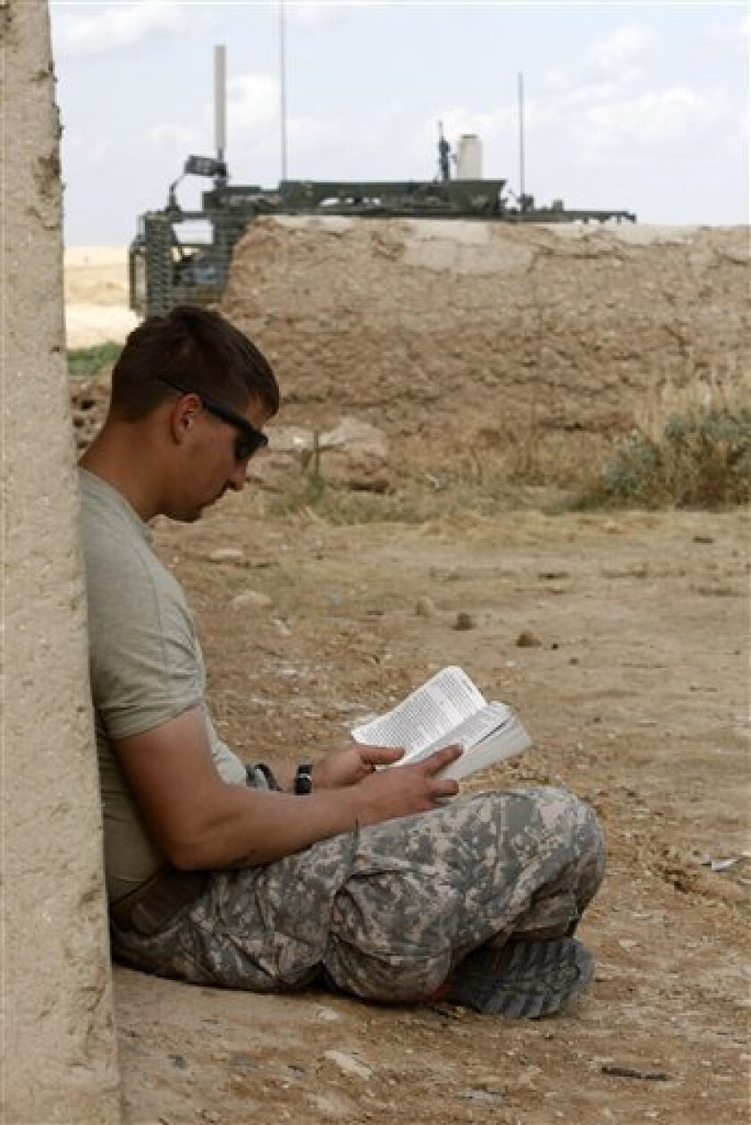 In this photo taken Monday, Feb. 22, 2010, Juan C. Diez of the U.S. Air Force reads a book during a pause from duty in an Army outpost in the Badula Qulp area, west of Lashkar Gah in Helmand province, southern Afghanistan. (AP Photo/Pier Paolo Cito)