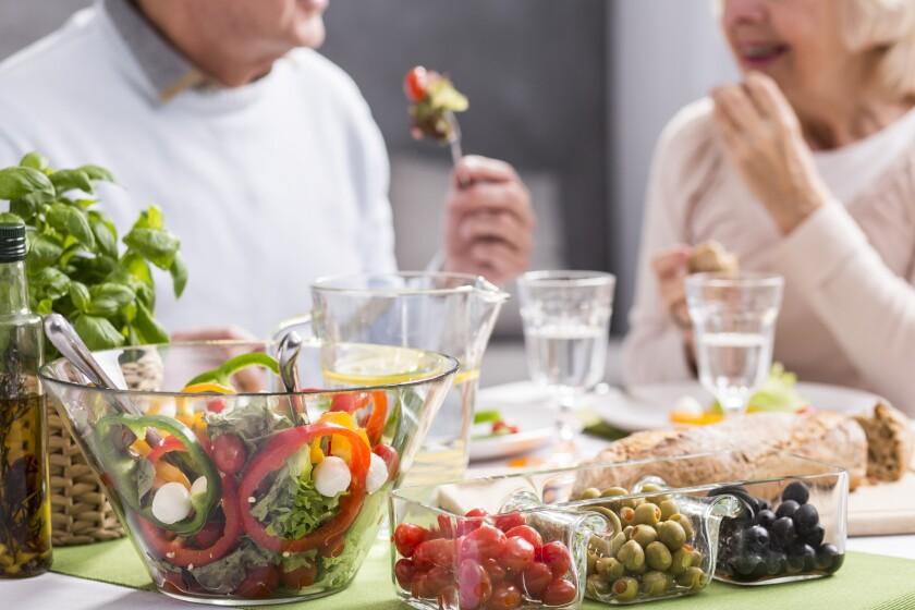Una pareja de adultos mayores disfruta alimentos sanos