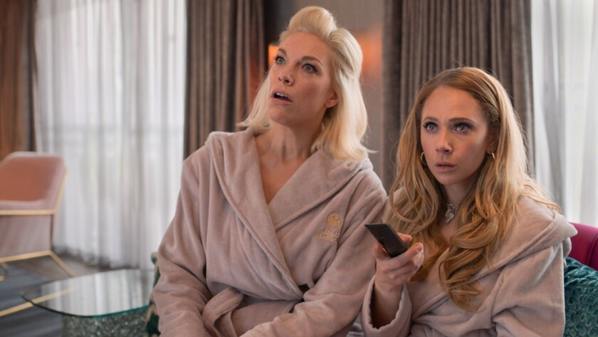 Two women in bathrobes looking up at a TV screen.