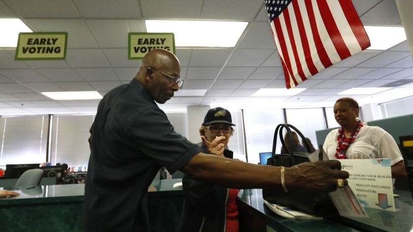 Billy Brown of Los Angeles drops his ballot in a box earlier this year at the Los Angeles County registrar-recorder's office in Norwalk.