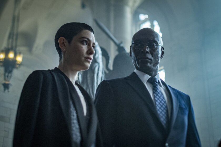 "(L-R)- The Adjudicator (Asia Kate Dillon) and Charon (Lance Roddick) in a scene from ""John Wick: Cha"
