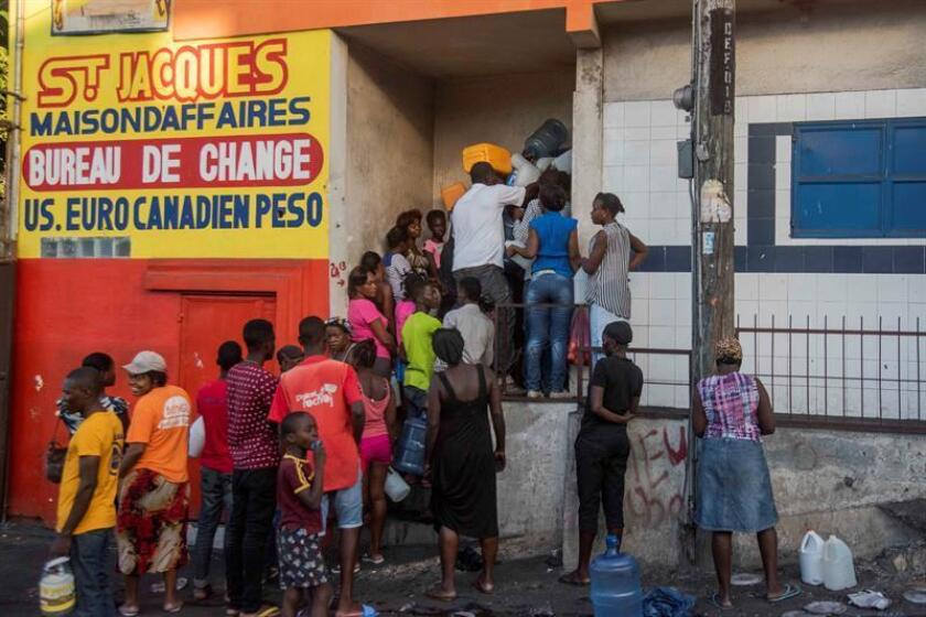 People queue to collect water in Port-au-Prince, Haiti, 14 February 2019. Many people have taken to the streets in search of water and food during the ongoing protests. The political and economic crisis in Haiti continues to worsen, eight days after the violent protests against the country's government broke out. EPA-EFE/JEAN MARC HERVE ABELARD