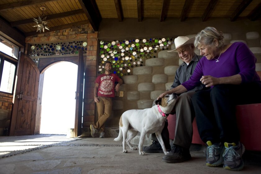 Sandra Moffat and construction foreman Jose Lara greet Moffat's dog Piedra inside the Rosarito Beach house she had built of recycled materials. In the background is the architect, Diego Colinas.