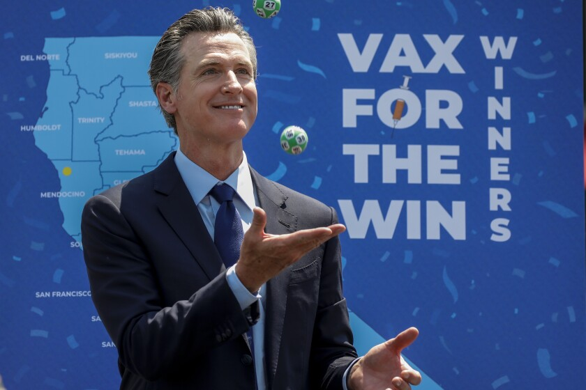 Gov. Gavin Newsom juggles numbered balls in front of a lottery sign.