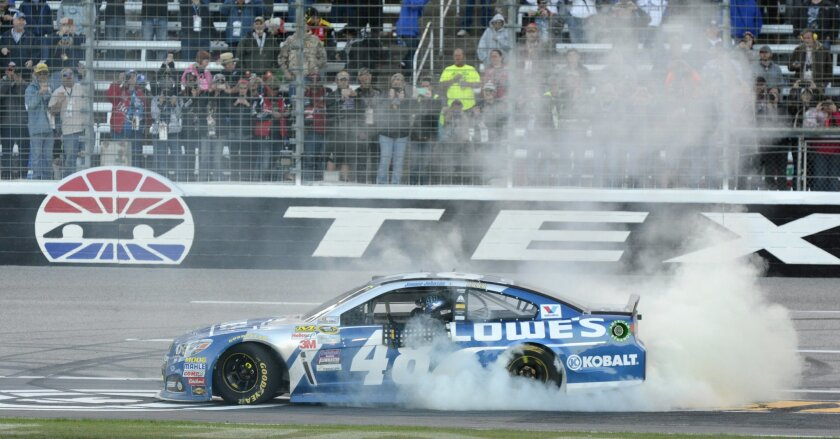 Jimmie Johnson (48) burns his tires celebrating winning the NASCAR Sprint Cup Series auto race at Texas Motor Speedway in Fort Worth, Texas, Sunday, Nov. 8, 2015. (AP Photo/Larry Papke)