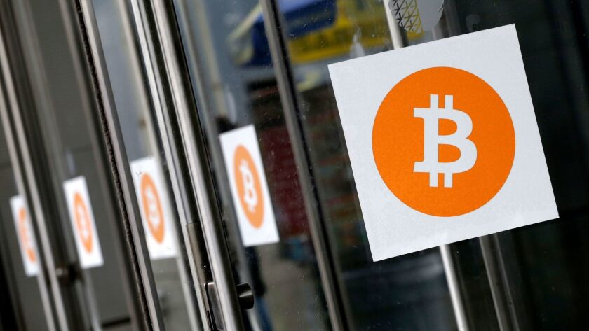 FILE - In this April 7, 2014, file photo, Bitcoin logos are displayed at the Inside Bitcoins conference and trade show in New York.