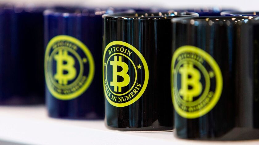 Mugs with the bitcoin logo are displayed for sale at La Maison du Bitcoin in Paris.