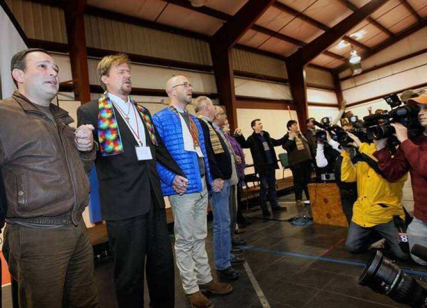 The Rev. Frank Schaefer, second from left, sings hymns with supporters after his church trial in Pennsylvania. He was found to have broken United Methodist Church law for performing the marriage of his gay son, and was given a 30-day suspension.