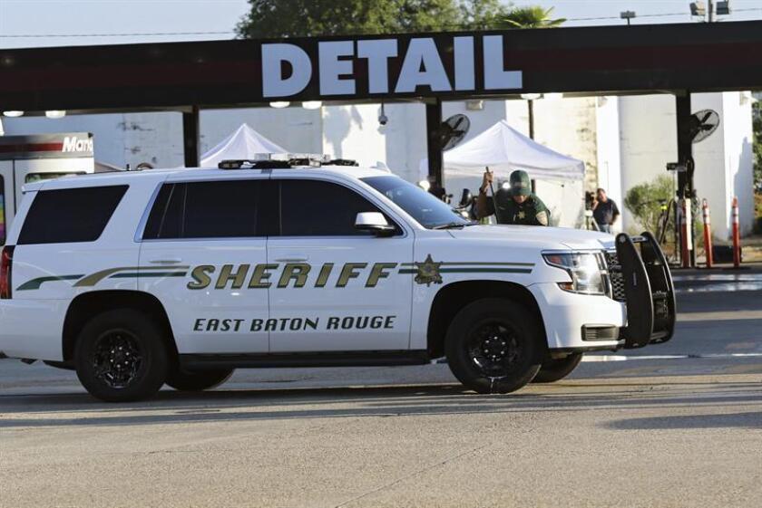 Un oficial del distrito de Baton Rouge limpia su vehículo. EFE/Archivo