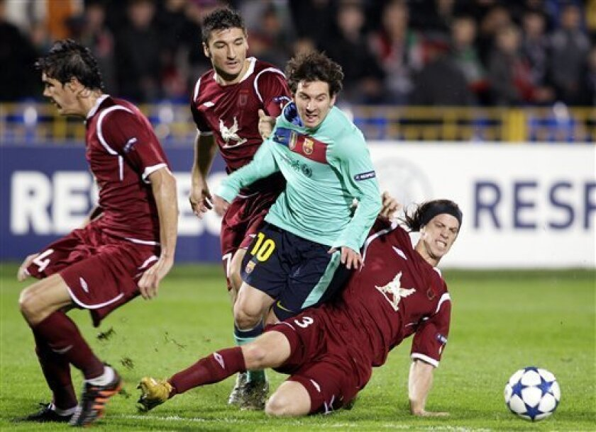 Barcelona's Lionel Messi, center, and Rubin Kazan's Cesar Navas, left, Salvatore Bocchetti, center, and Cristian Ansaldi struggle for the ball during their Champions League Group D soccer match in Kazan, Russia, Wednesday, Sept. 29, 2010. Game ended with a 1-1 draw. (AP Photo/Ivan Sekretarev)