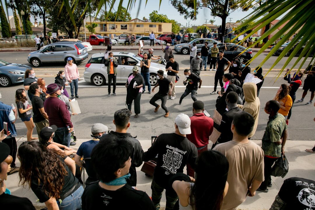 Breakdancers perform as a caravan of Black Lives Matter protesters drives past.