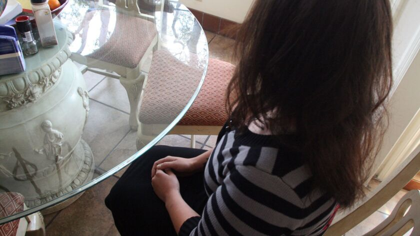 An unidentified patient sits at a dining room table at an area sober-living home in 2010.