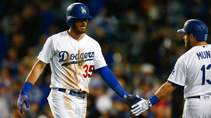 The Dodgers' Cody Bellinger (35) celebrates his score with teammate Max Muncy (13) during a game against the San Francisco Giants at Dodger Stadium on Wednesday.