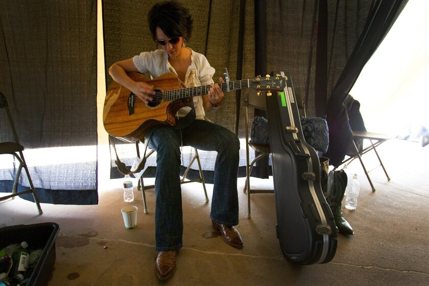 Singer songwriter, Ashley Matte relaxes by playing her guitar just before taking the stage at the Lilith Fair held at the Cricket Wireless Amphitheatre.