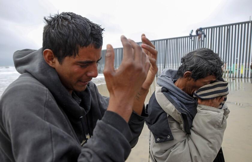 Los inmigrantes hondureños Marloh Cardona (derecha) y Gerson (quien solo dio su primer nombre) se limpian los ojos el jueves después de que los agentes estadounidenses los rociaron con pimienta en la cerca fronteriza de Playas de Tijuana.