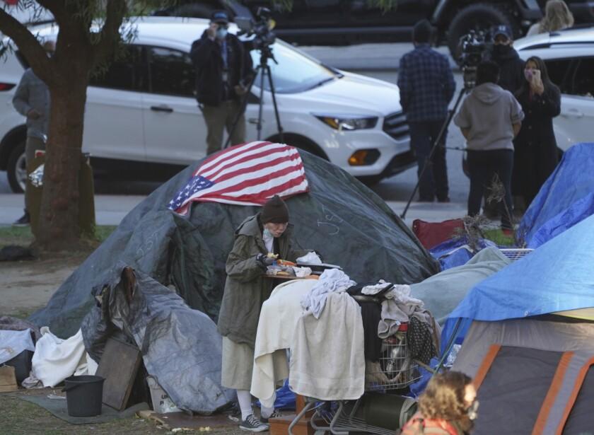 Una mujer come en su carpa en el campamento para indigentes de Echo Park Lake, Los Ángeles.