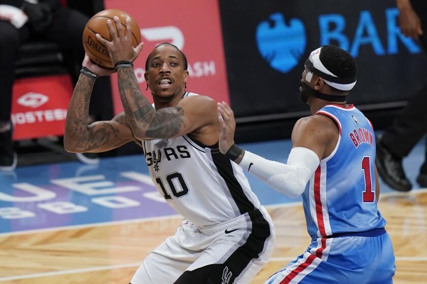 ARCHIVO - En esta foto de archivo del 12 de mayo de 2021, DeMar DeRozan, de los Spurs de San Antonio, amaga con disparar frente a Bruce Brown, de los Nets de Brooklyn (AP Foto/Frank Franklin II, archivo)