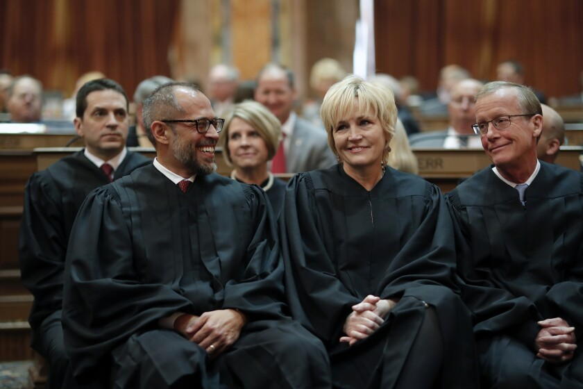 FILE - In this Jan. 14, 2020 file photo, Iowa Supreme Court Justices Christopher McDonald, left, Susan Christensen, center, and Edward Mansfield, right, attend Iowa Gov. Kim Reynolds' Condition of the State address at the Statehouse in Des Moines, Iowa. A divided Iowa Supreme Court on Friday, June 18, 2021, banned police from searching people's uncollected trash without a warrant, outlawing an investigative technique that had been used for decades. The court ruled 4-3 that officers commit an unreasonable search and seizure under the Iowa Constitution when they search for evidence of crimes in trash left for collection outside homes. (AP Photo/Matthew Putney, File)