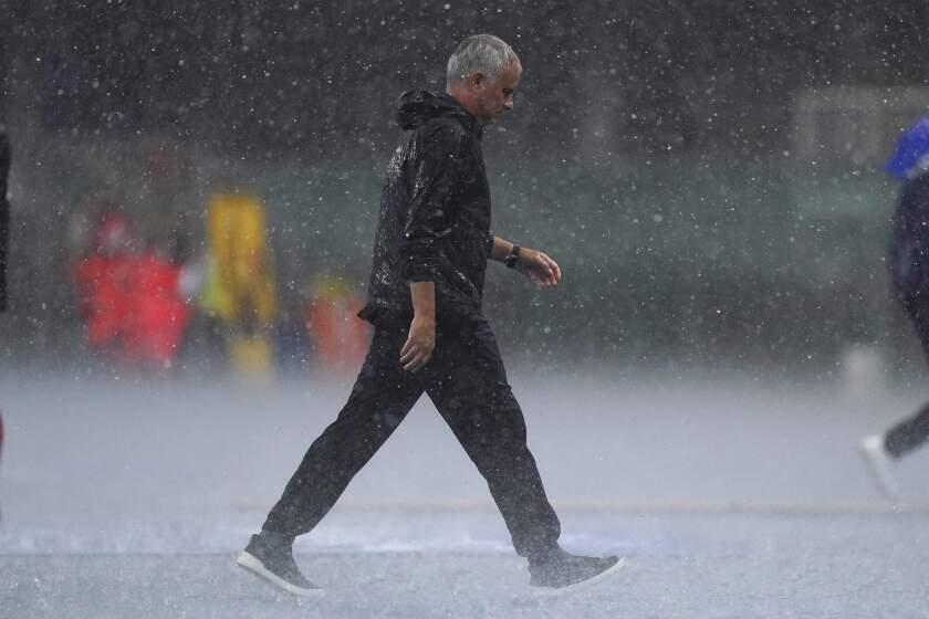 Roma coach Jose Mourinho runs under pouring rain during a Serie A soccer match between Hellas Verona and Roma, in Verona's Bentegodi Stadium, Italy, Sunday, Sept. 19, 2021. (Spada/LaPresse via AP)
