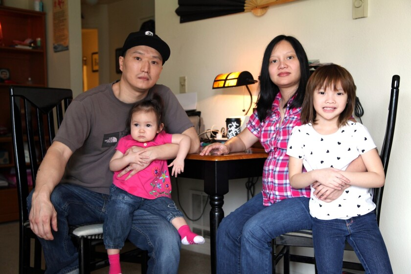 Korean adoptee Adam Crapser with his wife, Anh Nguyen, and daughters, Christal, 1, and Christina, 5, in the family's living room in Vancouver, Wash., in 2015.